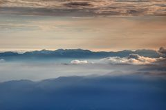 Ridge silhouettes in glowing autumn mist Bohinj Julian Alps. Mountain ridge silhouettes in glowing autumn mist and sea of clouds, South / Lower Bohinj Range Stock Images