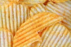 Ridged Cheddar Flavored Potato Chips. Ridged cheddar flaovred potato chips up close Royalty Free Stock Image