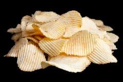 Ridged fried potato crisps. On black Royalty Free Stock Image