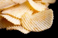 Ridged fried potato crisps. On black Royalty Free Stock Photo