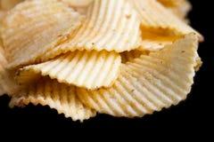 Ridged fried potato crisps. On black Stock Image