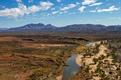 Finke River billabong under a cloudy sky. Ridges and mountains of the West MacDonnell National Park with the characteristic blue tonings showing in the mountains Stock Image