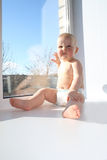 The ridiculous child sits on a window sill Royalty Free Stock Photos