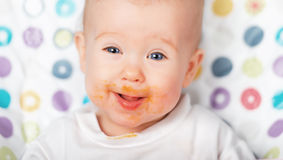 Funny baby eating dirty grimy Stock Image