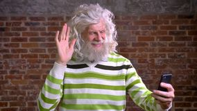 Ridiculous grandfather with white hair and bushy beard waving at web camera on phone and talking while standing isolated. On brick background stock video footage
