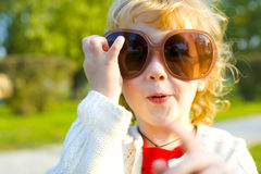 Ridiculous little girl puts on big sunglasses Stock Images