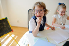 Ridiculous little students bespectacled, boy and girl, share the same desk. Stock Photography