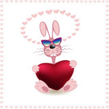 Ridiculous rabbit with heart in paws. The vector image of a ridiculous pink rabbit with red heart in paws on a white background with pink hearts Royalty Free Stock Photo