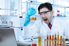 Ridiculous scientist with chemistry liquid Stock Photos