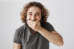 Ridiculously funny prices. Portrait of good-looking cheerful eastern man laughing and covering mouth with palm, watching. Comedy or hearing funny joke, standing stock image