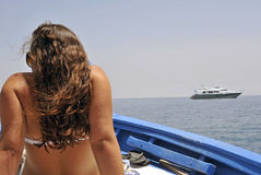 Riding. Boat ride: back of a girl seated on wooden prow to sunbath Stock Image
