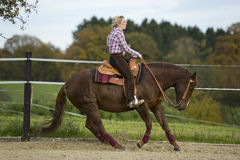 Riding. A woman is riding her horse Royalty Free Stock Image
