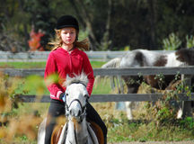 Riding. Young girl riding a white pony at countryside
