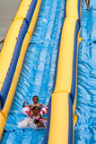 Riding 500-foot Waterslide. Grand Rapids, MI Aug 21: Unidentified children from the Grand Rapids area ride the 500-foot inflatable waterslide on Lyon street hill Royalty Free Stock Photo