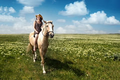 Riding. Outdoor photo of the young lady with hat riding on the horse Royalty Free Stock Photography