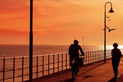 Riding along jetty at sunset to go fishing Royalty Free Stock Photos