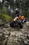 Riding ATV in mountains. Teen aged boy riding quad in the forest. Very difficult section of a rocky road Subject is approaching and facing camera Stock Image
