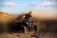Riding ATV - teen on quad. Teen riding ATV quad - four wheeler kicking up dirt Stock Images
