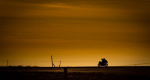Riding back home. Motor bike in on a road in the sunset Royalty Free Stock Photos