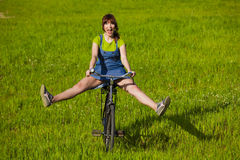 Riding a bicycle. Happy young woman on a green meadow riding a bicycle Stock Photos