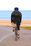 Riding bicycle. A person riding a bicycle on a seashore recreation trail stock photo