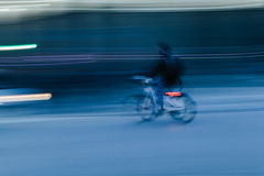 Riding a Bicycle in a Blurred City Scene Royalty Free Stock Photo