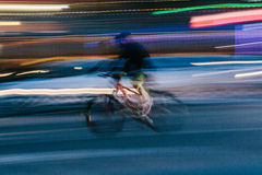 Riding a Bicycle in a Blurred City Scene Royalty Free Stock Photography