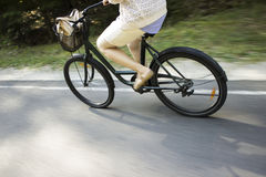Riding bicycle on the forest road. Close-up of woman riding bicycle Stock Photo