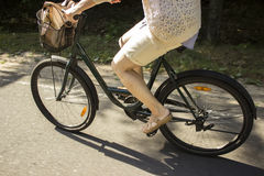 Riding bicycle on the forest road. Close-up of young woman riding bicycle. Royalty Free Stock Images