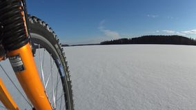 Riding bicycle on frozen lake stock video footage