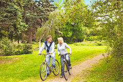 Riding bicycle. Happy couple biking together in the park Royalty Free Stock Image