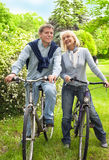 Riding bicycle. Senior couple on cycle ride in countryside Stock Image