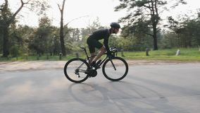 Riding a bicycle side follow view. Bearded man in black outfit on bicycle in the park. Out of the saddle pedaling. stock footage