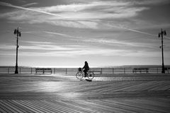 Riding a bicycle at the sunrise, Coney Island, New York Stock Photos