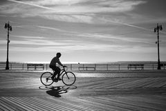 Riding a bicycle at the sunrise, Coney Island, New York Royalty Free Stock Images