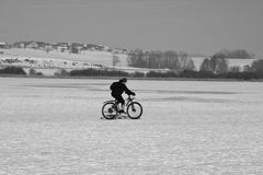 Riding bicyle on a frozen lake. Austria, Europe. Seekirchen, Austria –January 29, 2017: A woman is riding her bicycle on the frozen lake Wallersee in Royalty Free Stock Photo