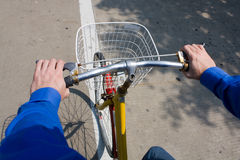 Riding a Bike. A man riding a bike with a view of his hands on the handle bars Stock Image