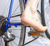 Riding a bike with bare foot. Stock Image