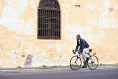 Riding bike black man. Black african mad riding bicycle in urban city commuting with speed and hipster trendy transportation Stock Photos