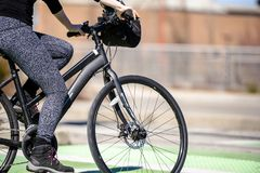 Woman in leggings and boots riding bicycle taking care of her health royalty free stock photos