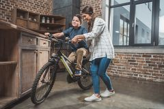 Young mother teaching her son how to ride a bicycle royalty free stock image