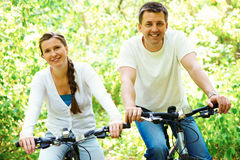 Riding bikes. Photo of happy husband and wife riding bicycles outdoors Royalty Free Stock Images