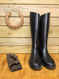 Riding boots and gloves in a stable Royalty Free Stock Photos
