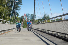 Riding On The Bridge. A young family rides across the Peter DeFazio Bike Bridge crossing the Willamette River in Eugene Oregon Royalty Free Stock Images