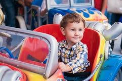 Riding a car. Little boy riding a car in amusement park Stock Photos