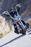 Riding a chopper motorbike. Closeup of a chopper motorcyclist driving his motorcycle by a mountain road at sunrise - focus on the face royalty free stock image