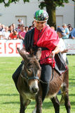 Riding a donkey contest Stock Photo