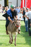 Riding a donkey contest Royalty Free Stock Image