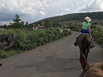 Horseback Riding in Mexico. Riding down a road in rural Mexico Stock Image