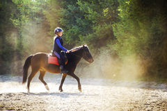 Riding in dust. A young girl riding her pony during riding lesson, outside. Natural sun rays shining in dust during sunset Royalty Free Stock Photo